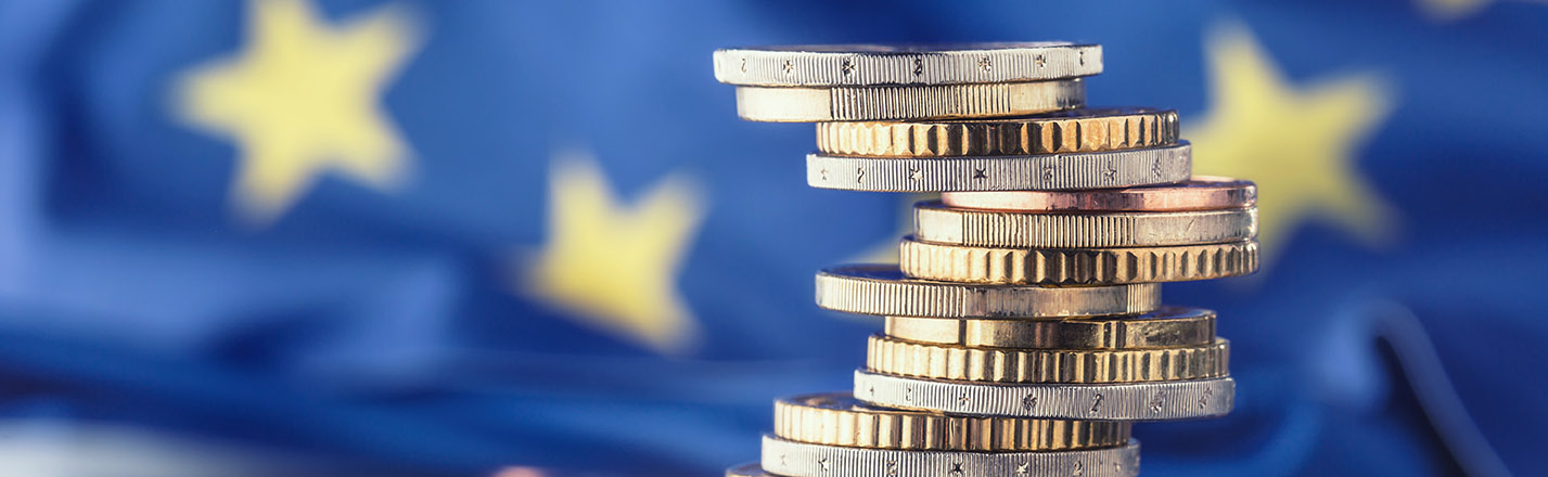 European Union flag with a stack of coins in the foreground