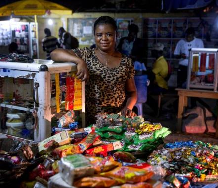 A young Ghanian woman stands proudly at her snack cart