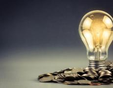 An image of a lightbulb with coins.