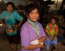 Three Thai women look into the camera from their office