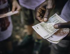 A close up of a man sorting cash