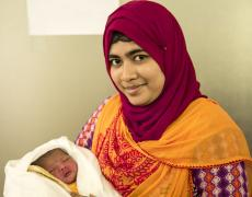 Tania, a midwife for UNFPA in Kutapalong refugee camp, holds a newbord baby