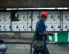 """A man in a face mask walks past a stadium bus stop with posters titled """"coro must go"""" in Lagos, Nigeria"""