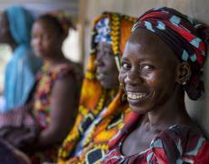 A group of women smile outside a health center in Lanier, Senegal