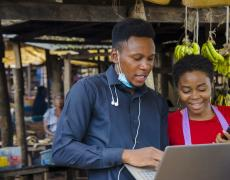 A young man in a blue shirt shoes a woman in a red shirt something on his laptop in an outdoor market in Nigeria