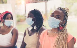 An image of three young black women wearing masks.