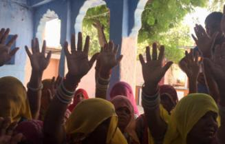 Aadhaar survey respondents give a show of hands when discussing issues with receiving rations
