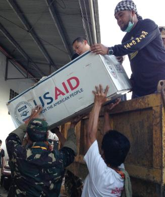 USAID relief supplies are unloaded after Typhoon Haiyan. Photo by Carol Han, OFDA, USAID
